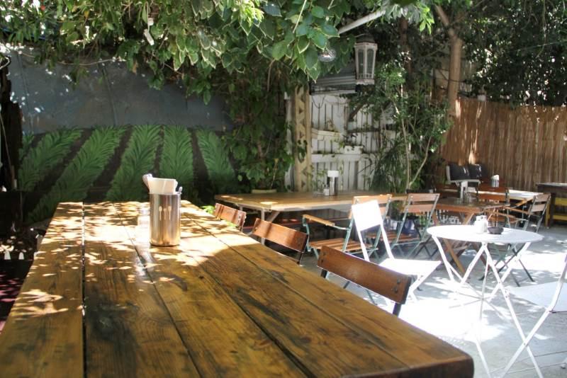 """""""גן ירקרק ופסטורלי, בסגנון כפרי ונעים, עם ציורים על הקירות ושולחנות ארוכים מעץ – בוסתן"""". בתמונה: חצר 'בוסתן 15'   צילום: מעין אמרן"""